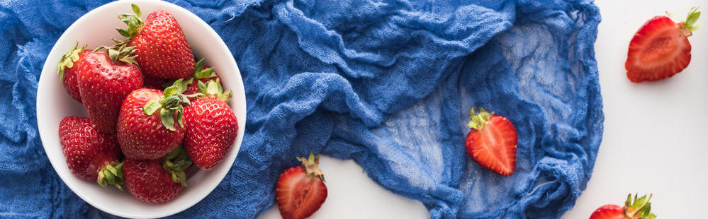 Panoramic shot of fresh and ripe strawberries on bowl with blue cloth